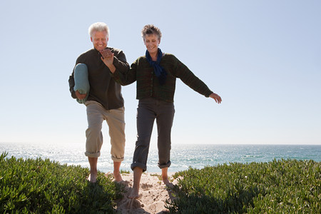 travel features: Mature couple walking over dune LANG_EVOIMAGES