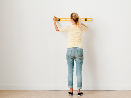 Young woman using spirit level on wall LANG_EVOIMAGES