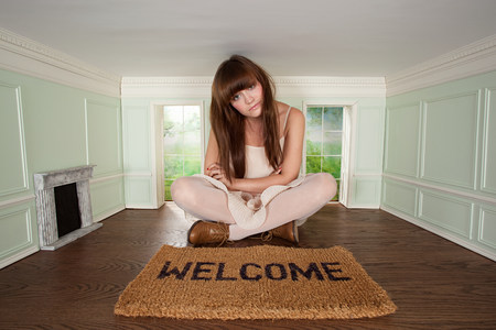 housing lot: Young woman sitting in small room with welcome mat