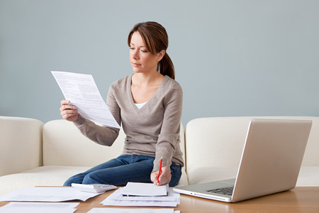 only 1 woman: Young woman with paperwork using laptop