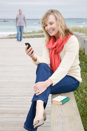 electronic book: Woman at the coast with smartphone