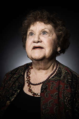 70 75: Studio portrait of senior woman looking up
