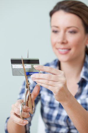 endings: Young woman cutting credit card