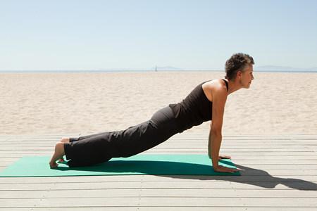 Senior woman doing yoga on beach