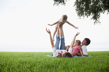 Girl balancing on feet of mother