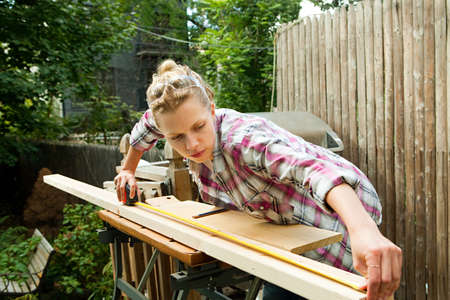 home decorating: Woman measuring plank of wood