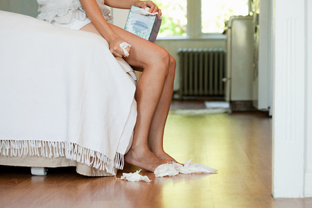 Legs of woman on bed with tissues on floor LANG_EVOIMAGES