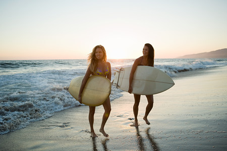 cheer full: Female surfers by the sea at sunset