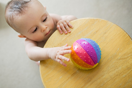 Baby reaching for toy LANG_EVOIMAGES