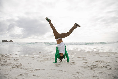 impulsive: Young man doing cartwheels on beach