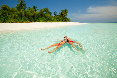 Couple floating in the sea, Baughagello Island, South Huvadhu Atoll, Maldives