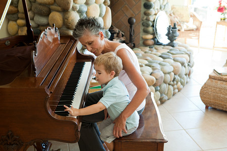 60 64 years: Grandmother and grandson playing the piano