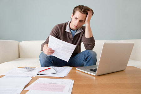 arrears: Worried young man with paperwork using laptop LANG_EVOIMAGES