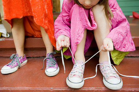 low section: Two girls, one tying up shoelace