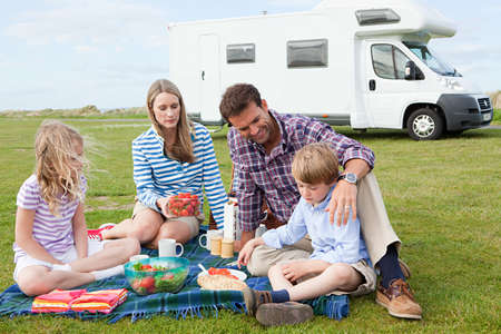 6 7 year old: Family having picnic by caravan LANG_EVOIMAGES