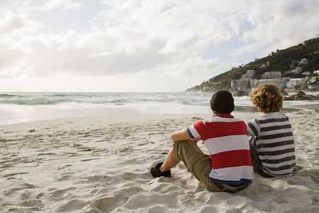 19 year old boy: Two boys sitting on beach