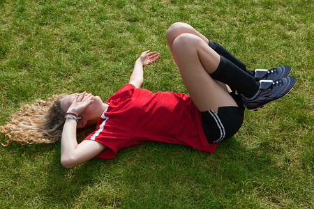 strip shirt: Girl soccer player with injury LANG_EVOIMAGES