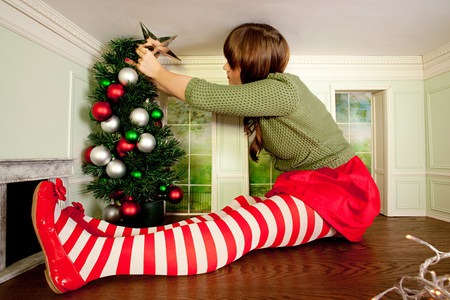 housing lot: Young woman in small room decorating christmas tree