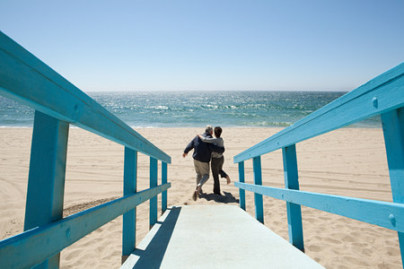 Rear view of couple on beach walkway