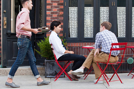 25 29 years: Waiter bringing coffee to men outside cafe