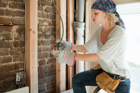 home decorating: Woman wearing protective gloves working with wiring LANG_EVOIMAGES