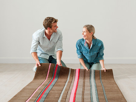 coverings: Young couple unrolling rug on floor LANG_EVOIMAGES