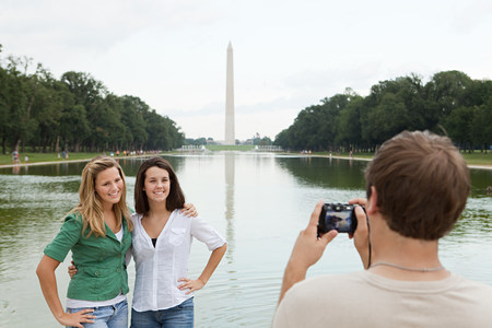 Young man taking photograph of friends at washington monument LANG_EVOIMAGES