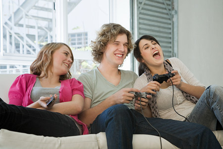 Teenagers playing on games console