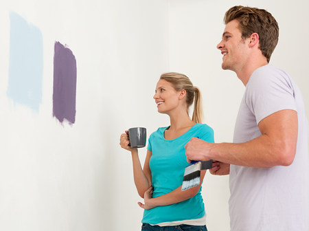 purples: Young couple looking at paint on wall LANG_EVOIMAGES