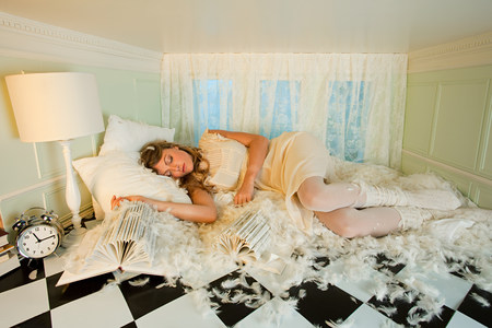 housing lot: Young woman sleeping amongst pillow feathers in small room
