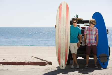 Two young men at coast with surfboards LANG_EVOIMAGES