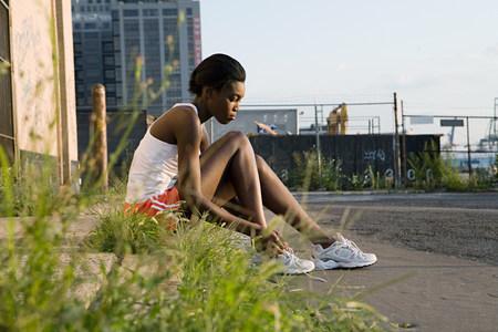 Runner sitting on sidewalk LANG_EVOIMAGES