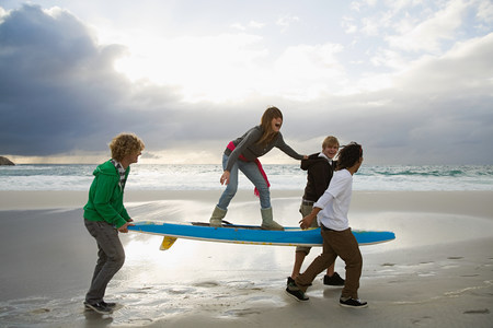 Young people carrying surfboard, person balancing on top