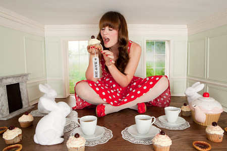 Young woman eating cake at tea party in small room
