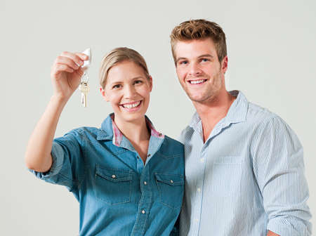 first time buyer: Young couple holding house keys LANG_EVOIMAGES
