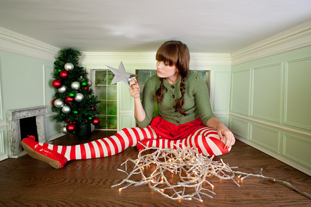 housing lot: Young woman in small room with christmas decorations LANG_EVOIMAGES
