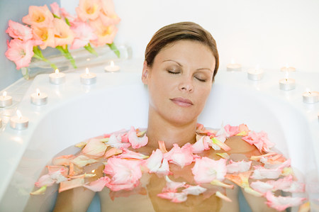 Young woman in bath with petals