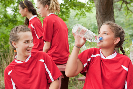 Girl soccer players drinking water