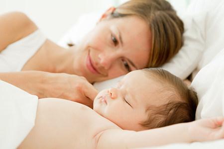 snoozing: Mother watching baby girl sleep