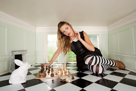 Young woman playing chess with rabbit LANG_EVOIMAGES