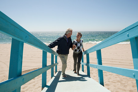 travel features: Mature couple walking on beach walkway