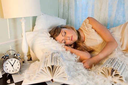 housing lot: Young woman sleeping amongst pillow feathers LANG_EVOIMAGES