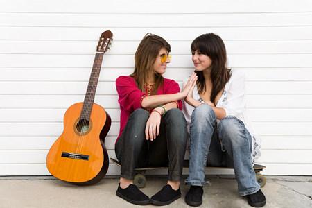 Dos chicas sentadas en el piso con guitarra LANG_EVOIMAGES