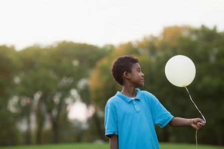 Boy at birthday party holding balloon LANG_EVOIMAGES
