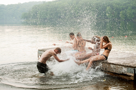 Mid adult man splashing friends in lake