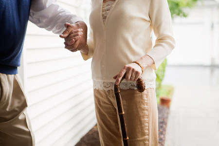 help section: Senior couple standing with walking stick