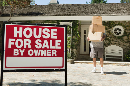 exerting: Mature man carrying boxes to move into newly bought property