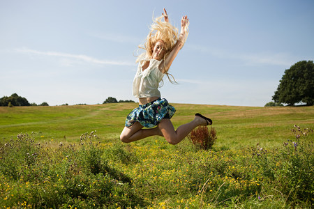 Young woman in a field, jumping in the air