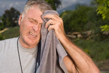 Senior hombre limpiando la cara con una toalla después del ejercicio