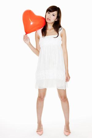 miserable: Woman holding red heart shaped balloon, studio shot